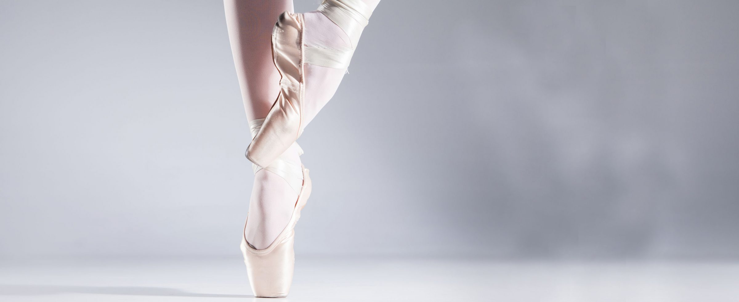 Legs of a graceful ballet dancer en pointe on toes.